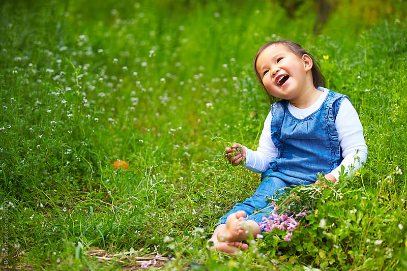lovely little asian girl sitting in the grass at spring day by Bo Bo for Stocksy United