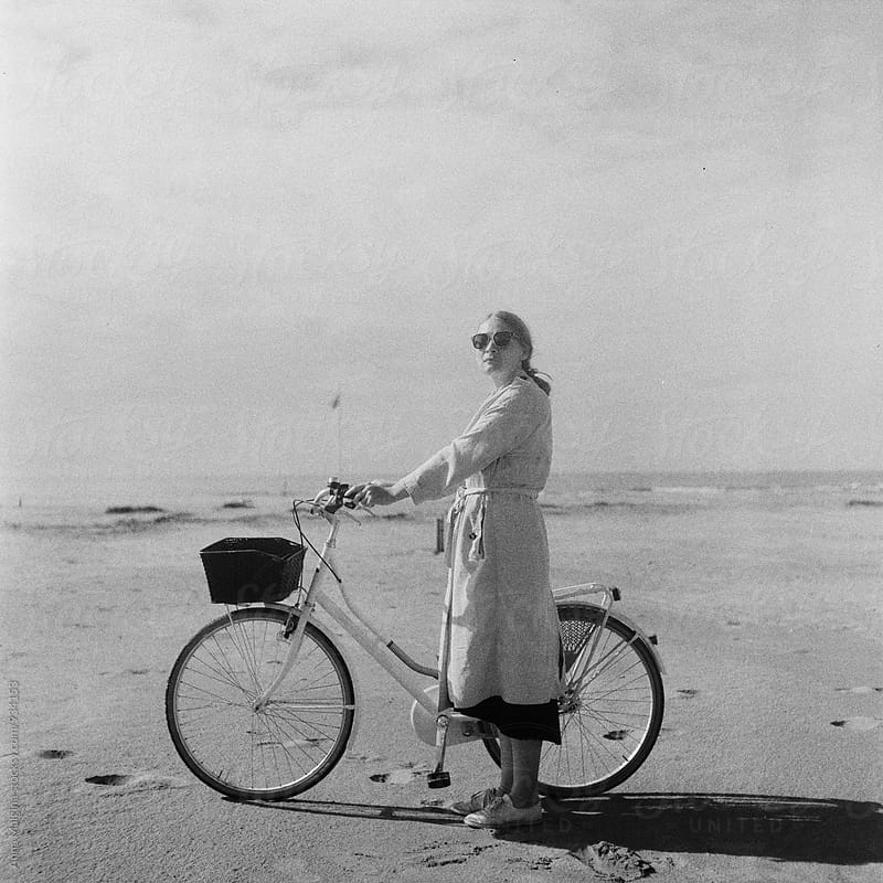 A black and white film portrait of a young beautiful woman with a bicycle on the beach by Anna Malgina for Stocksy United
