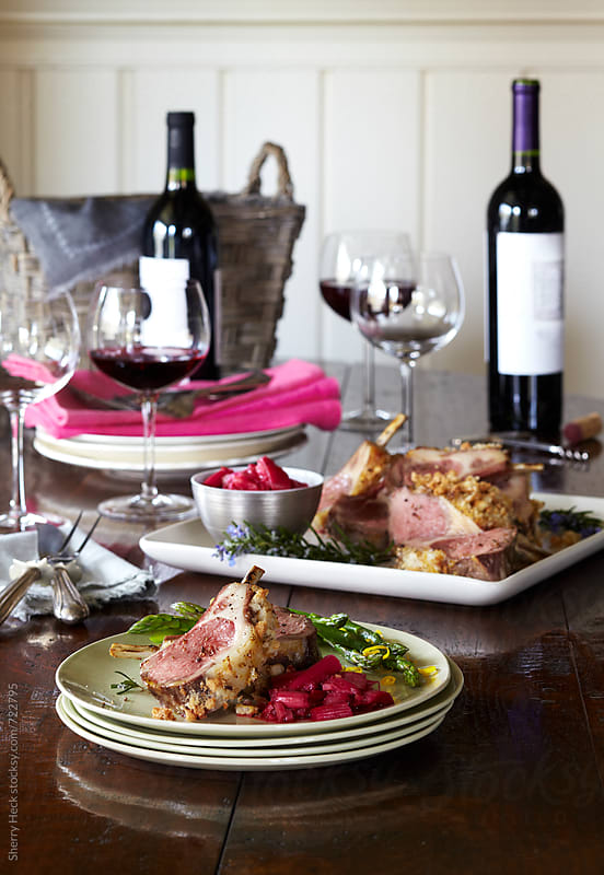 A plate of food ready for guest with wine and platter of lamb in background by Sherry Heck for Stocksy United