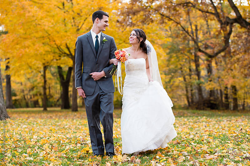 bride and groom in autumn by Brian Powell for Stocksy United