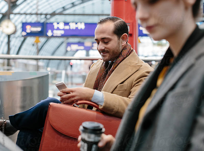 Commuting Businessman Checking Emails On Smart Phone by VegterFoto for Stocksy United