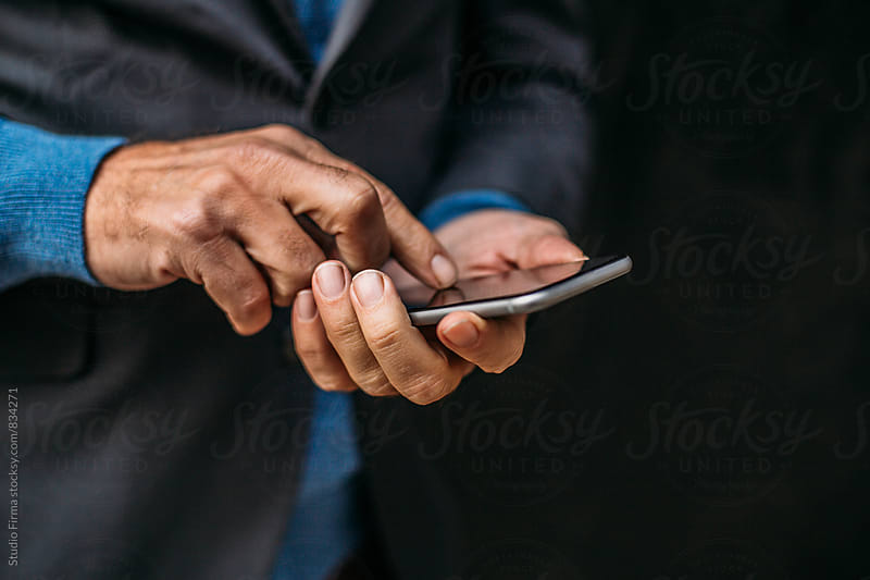 Businessman Holding His Phone by Studio Firma for Stocksy United