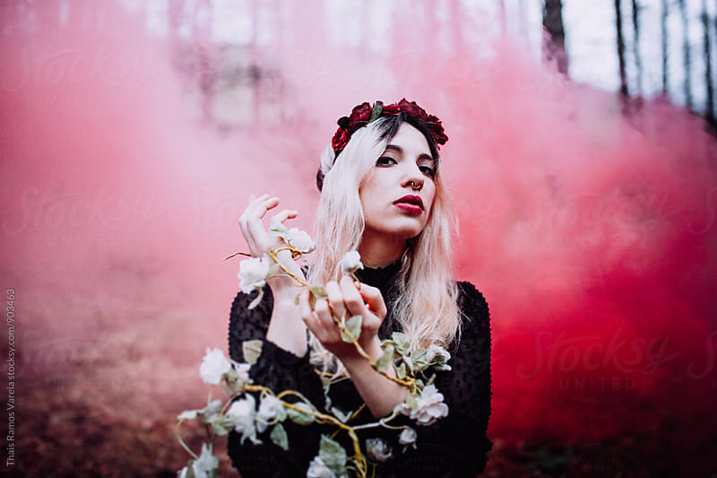 young woman with the red smoke in the woods  by Thais Ramos Varela for Stocksy United