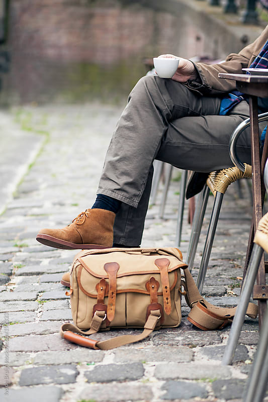 Close up of someone's legs enjoying a coffee on a terrace on a cobblestone road in Amsterdam by Ivo de Bruijn for Stocksy United