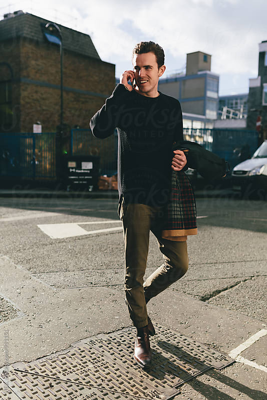 Young businessman walking in the street in London by HEX. for Stocksy United