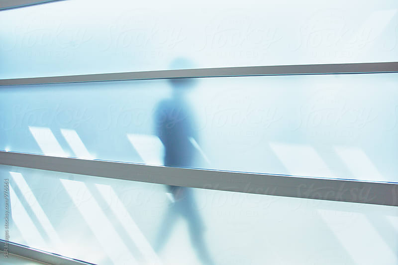 Person walking outside opaque glass wall in an office by Per Swantesson for Stocksy United