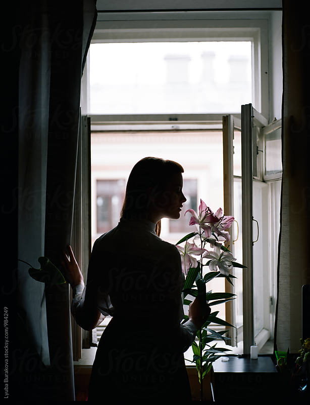 Silhouette of the woman holding lily flower by Liubov Burakova for Stocksy United