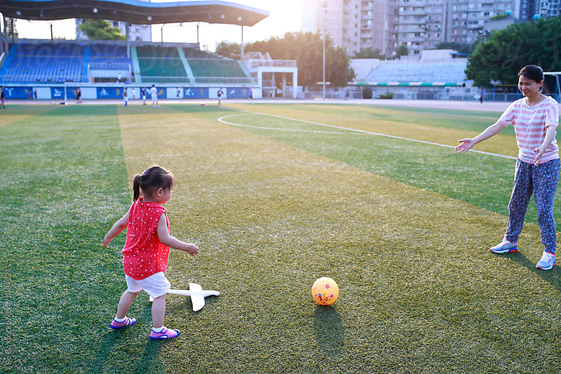 little asian girl playing with her mother outdoor in the playground by cuiyan Liu for Stocksy United