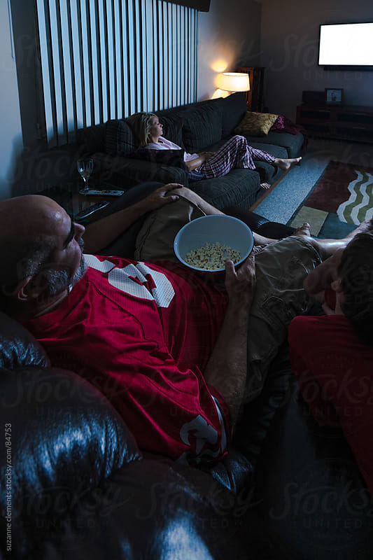Family Enjoys Time Together Watching TV by suzanne clements for Stocksy United