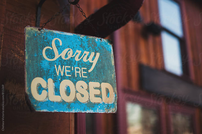 A sorry we're closed sign outside of a shop by Chelsea Victoria for Stocksy United