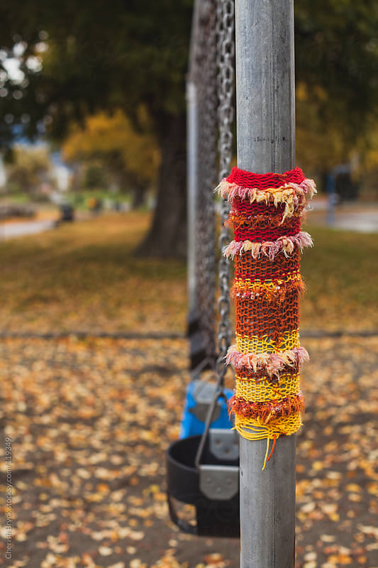 A yarn bomb at a children's swing set. by Cherish Bryck for Stocksy United