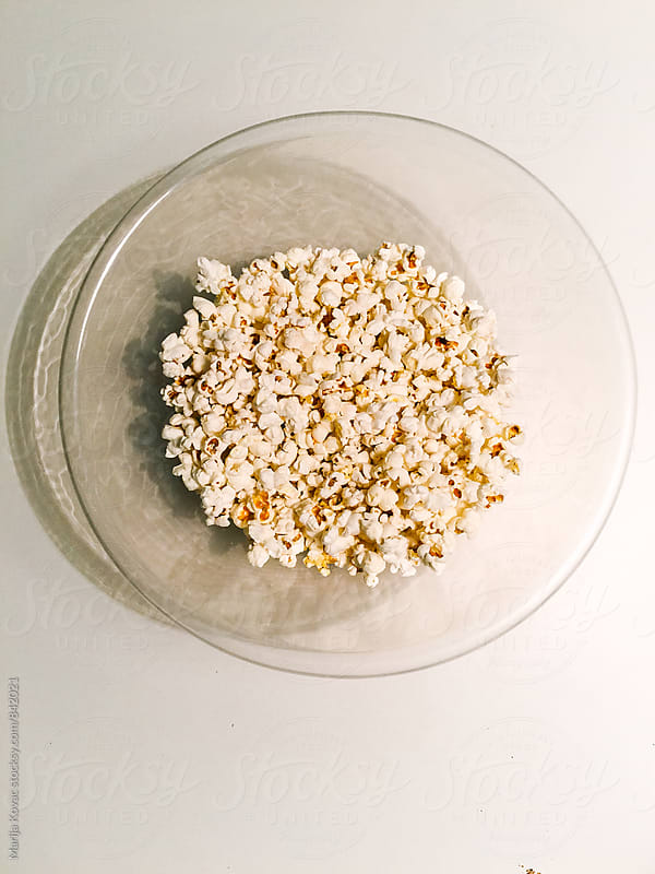Popcorn in a bowl on a white table, from above - vertical by Marija Kovac for Stocksy United