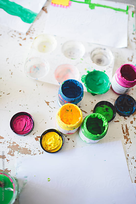 table top view of colourful paints by Natalie JEFFCOTT for Stocksy United
