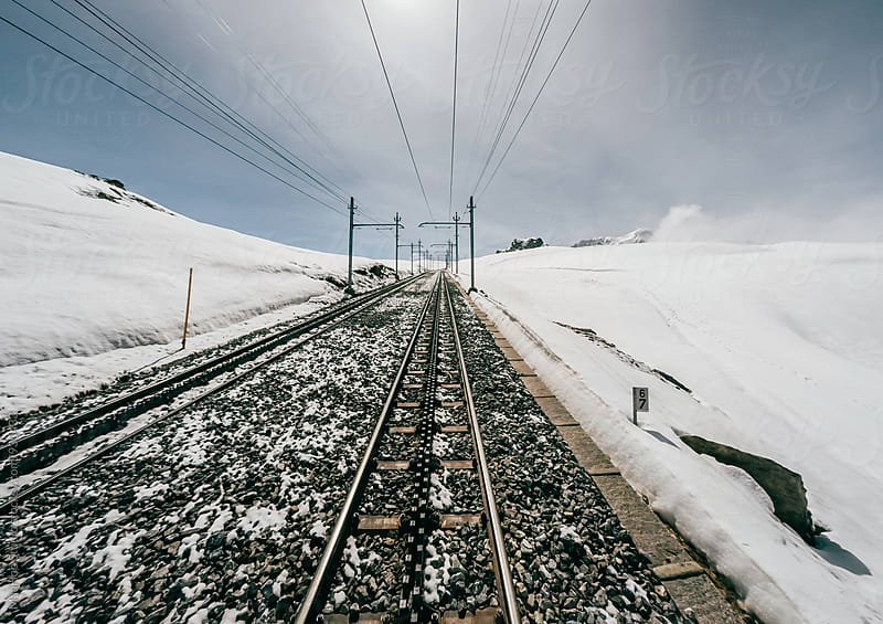 Driver view of train crossing snow mountain by MaaHoo Studio for Stocksy United