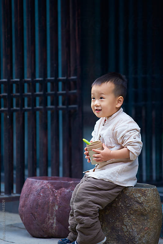 lovely asian boy holding his lunch outdoor by Bo Bo for Stocksy United