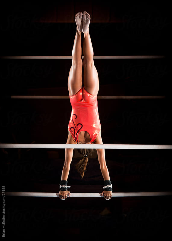 Female gymnast in hand stand atop uneven bars by Brian McEntire for Stocksy United