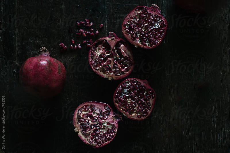 Cut pomegranate styled on dark wood table by Daring Wanderer for Stocksy United