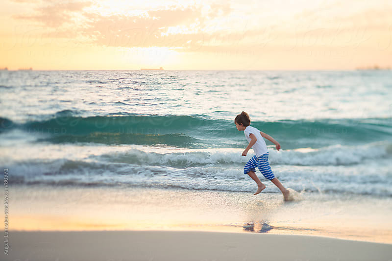 Boy playing at the beach at sunset by Angela Lumsden for Stocksy United