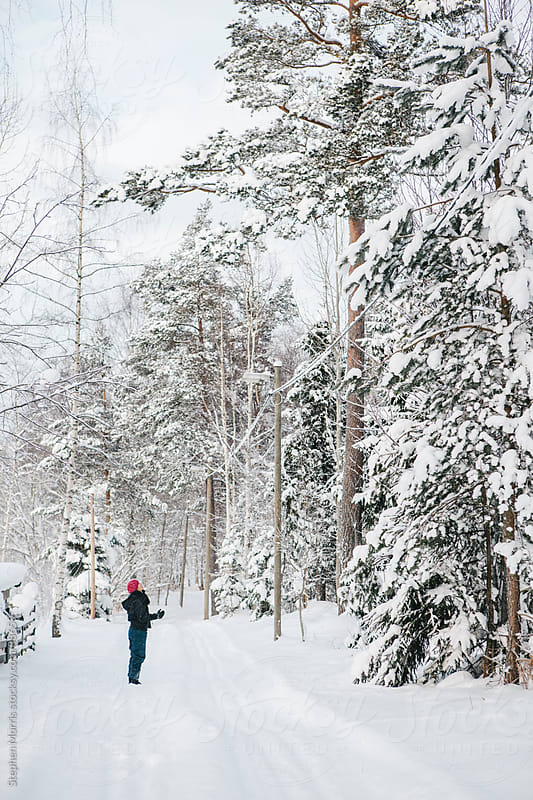 Woman looking up on in snowy forest by Stephen Morris for Stocksy United