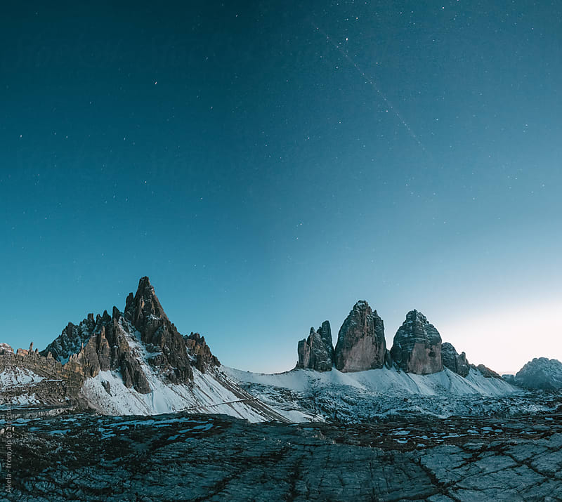 panorama shot of the famous three peaks during the blue hour with a starry night by Leander Nardin for Stocksy United