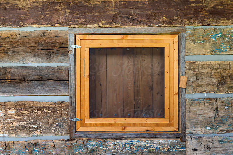 Window of a log cabin with interior shutter closed by David Smart for Stocksy United