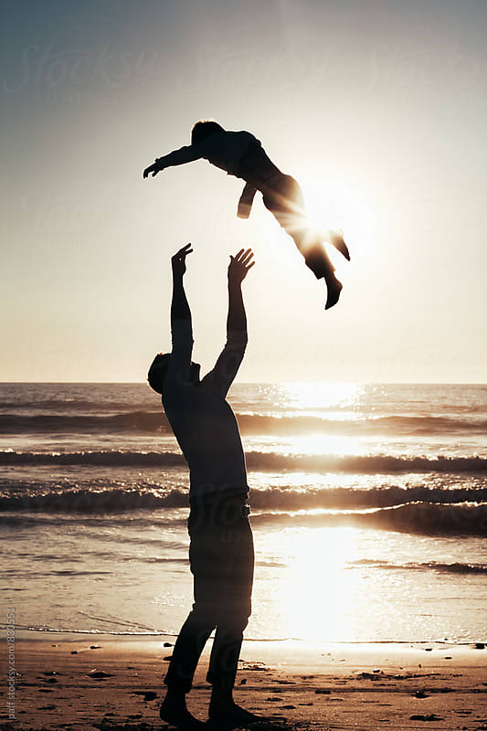 Silhouette of an young father playfully tossing  his son up into the air by paff for Stocksy United