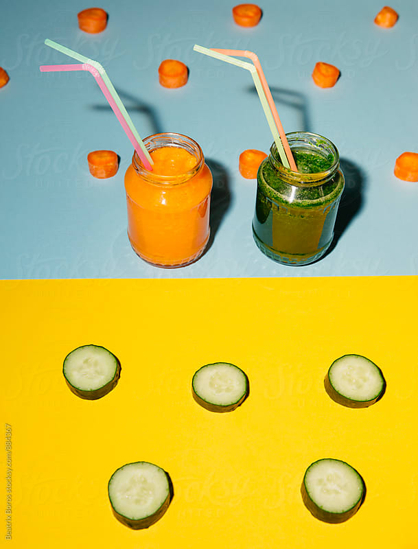 Healthy smoothies in jars with cucumber and carrot slices around them by Beatrix Boros for Stocksy United