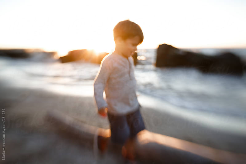 child walks on beach at sunset by Maria Manco for Stocksy United
