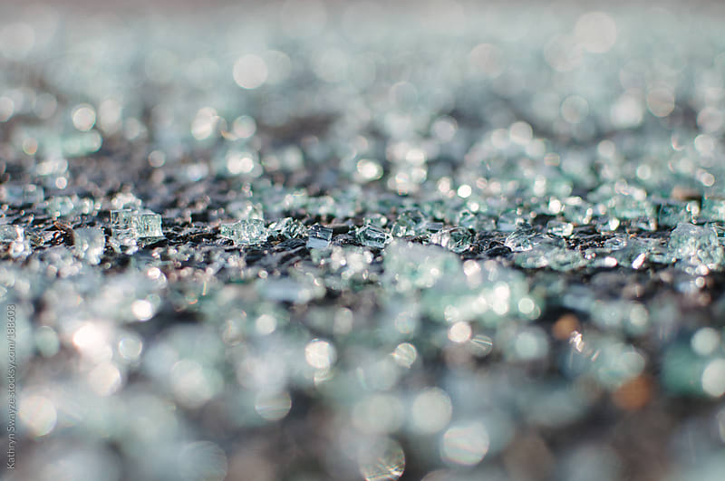 Close-up of shattered windshield glass on pavement by Kathryn Swayze for Stocksy United