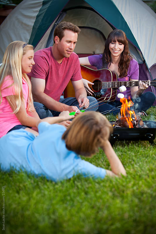 Camping: Family Cooking Marshmallows Over Campfire by Sean Locke for Stocksy United