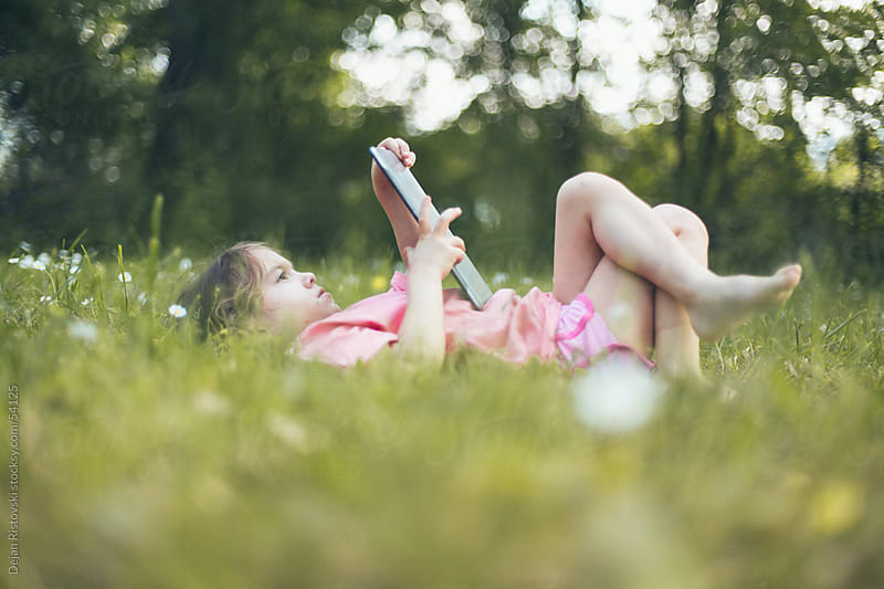Child lying on  grass ,reading on a digital tablet by Dejan Ristovski for Stocksy United