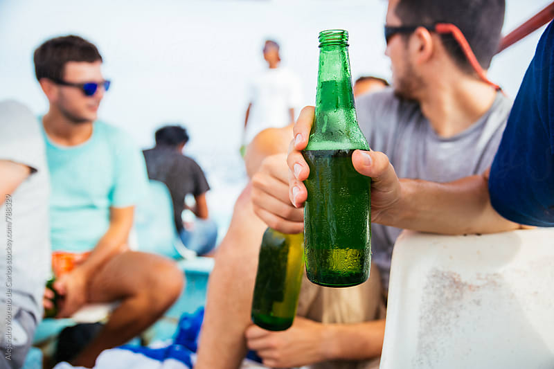 Front view of a man's hand holding a green beer bottle with a group of young men relaxing in the background by Alejandro Moreno de Carlos for Stocksy United
