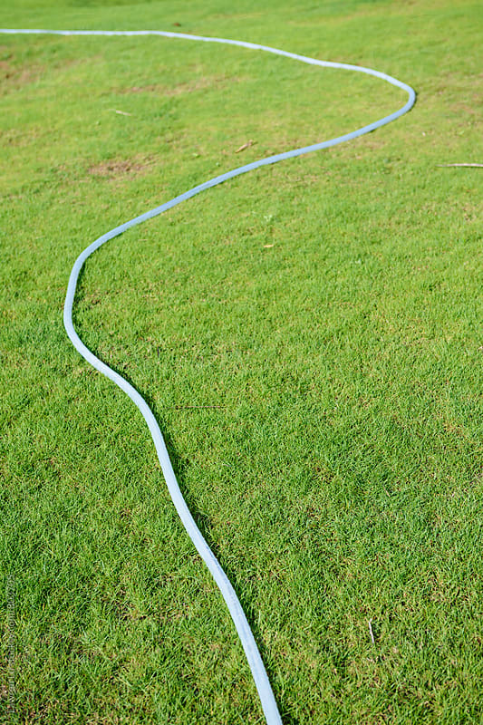 Watering pipes on green grass by Lawren Lu for Stocksy United