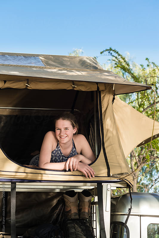 teen girl inside a roof top camping tent by Gillian Vann for Stocksy United