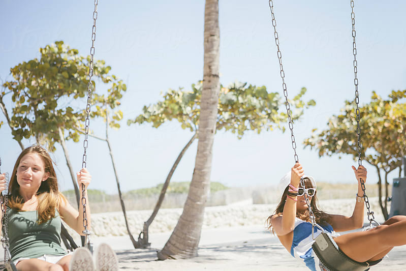 Two College Student Women Friends Having Fun on Swing during Spring Break in Miami by Joselito Briones for Stocksy United