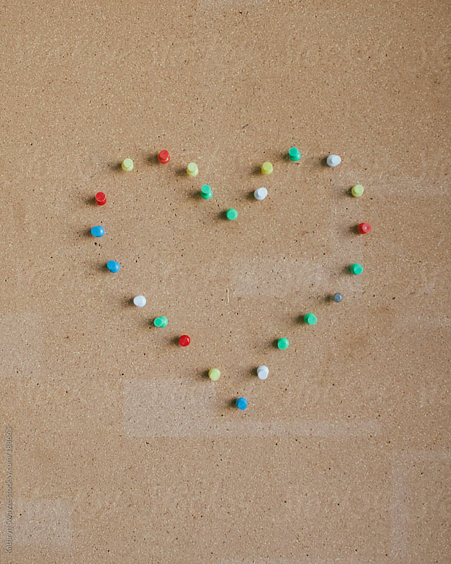 Thumb tacks pressed into bulletin board, forming a heart shape by Kathryn Swayze for Stocksy United
