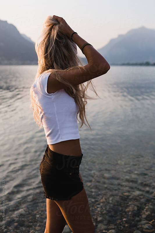 Young beautiful woman walking in the lake, in summer by michela ravasio for Stocksy United