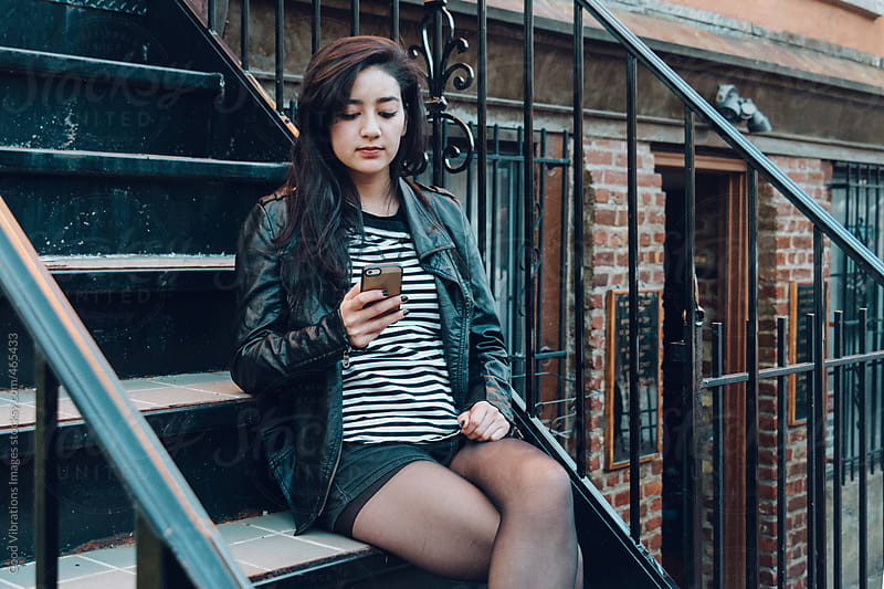 Woman with cell phone outdoors by Good Vibrations Images for Stocksy United