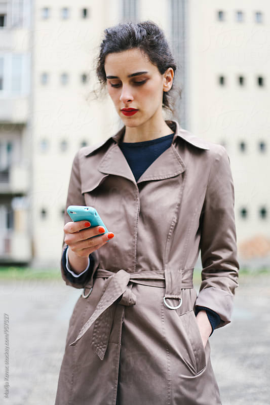 Brunette woman holding a cell phone by Marija Kovac for Stocksy United