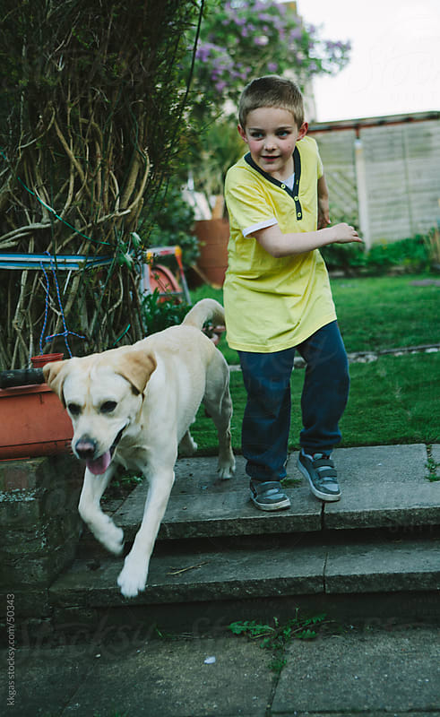 Young boy playing with his dog by kkgas for Stocksy United