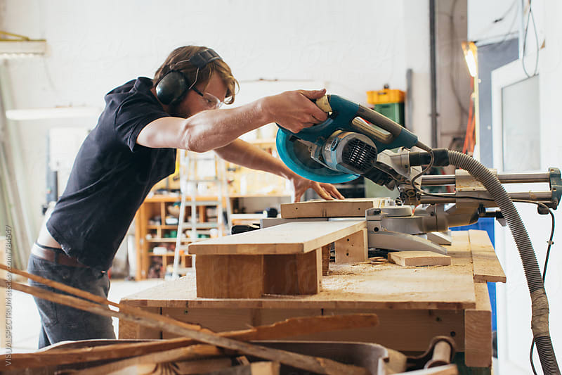 Young Male Carpenter Using Circular Saw in Bright Workshop by VISUALSPECTRUM for Stocksy United