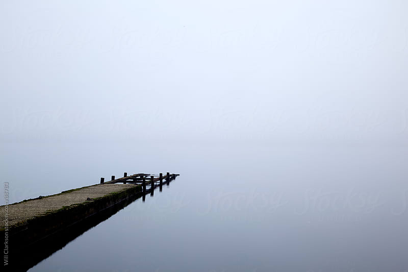 Pier leading into a misty lake by Will Clarkson for Stocksy United