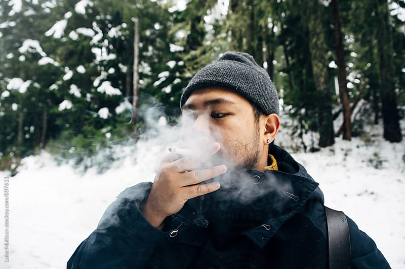 Man In Beanie Standing In Snowy Forest Smoking Cigarette by Luke Mattson for Stocksy United