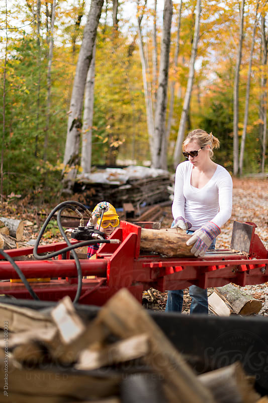 Woman and Boy Splitting Firewood for Heating In Fall at Cottage by JP Danko for Stocksy United