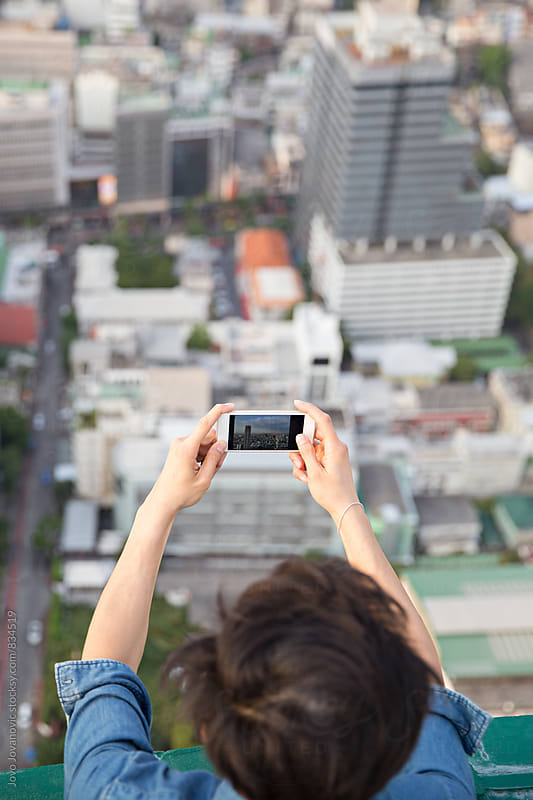 Man taking a photo of the city center from above by Jovo Jovanovic for Stocksy United