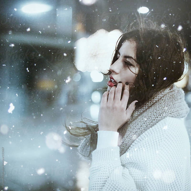 Woman with hand raised to face in a snowfall by Jovana Rikalo for Stocksy United
