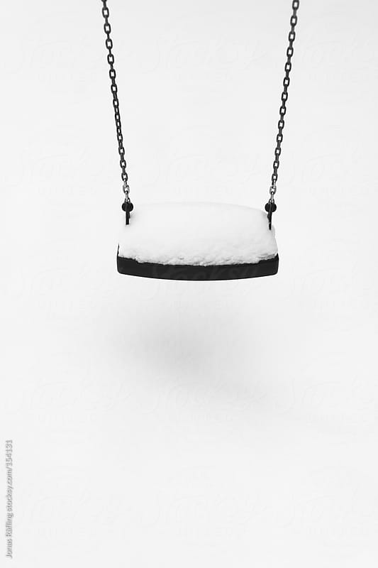 Swing full of snow by Jonas Räfling for Stocksy United