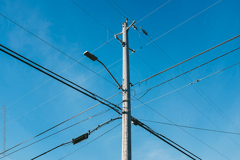 Telephone pole and power lines by Paul Edmondson for Stocksy United