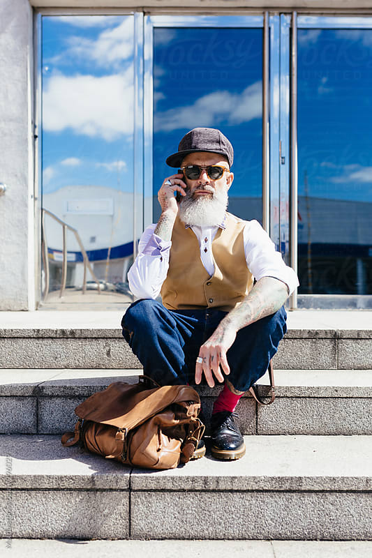 Eccentric Stylish Man Using His Phone Outdoor by HEX. for Stocksy United