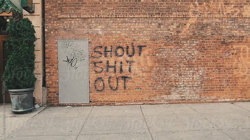 A City Sidewalk With Profanity Graffiti On Brick Wall By Greg Schmigel For Stocksy United